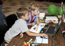Ethan Hicks and Eric Mellin of Starkville follow instructions to program the soccer goalie robot they built at the Cloverbud Camp held at Mississippi State University. (Photo by MSU Ag Communications/Scott Corey)