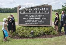 About 200 former colleagues, friends and family members attended the dedication of the Frank T. (Butch) Withers Jr. Central Mississippi Research and Extension Center held July 10 in Raymond. Withers' family members Jaidyn Laird, Caroline Withers, Shelly Withers and Elizabeth Kilgore, along with Mississippi State University President Mark Keenum (at left) and Vice President of the Division of Agriculture Forestry and Veterinary Medicine Greg Bohach, look on as the new sign is revealed. (Photo by MSU Ag Commu