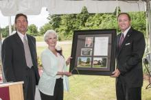 Vice President of the Division of Agriculture Forestry and Veterinary Medicine Greg Bohach, left, and Mississippi State University President Mark Keenum present Caroline Withers with a framed collage to commemorate the dedication of MSU's Frank T. (Butch) Withers Jr. Central Mississippi Research and Extension Center. A duplicate will hang inside the center. Withers and daughters Elizabeth Kilgore and Shelly Withers also received engraved cowbells as mementos of the occasion. (Photo by MSU Ag Communications/
