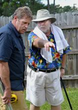 """Gary Bachman (right), horticulture expert with Mississippi State University, reviews information with """"Ask This Old House"""" landscape contractor Roger Cook. Bachman provided off-camera expertise for the segment filmed by the traveling home improvement show on Oct. 9 in Biloxi. The crew also recorded segments for the current season in Mobile on Oct. 8 and in New Orleans on Oct. 10. (Photo by MSU Ag Communications/Susan Collins-Smith)"""