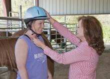 As a safety precaution, Anna Imel, left, has her riding helmet adjusted by Lori Irvin, a therapeutic riding instructor at the 4-H Elizabeth A. Howard Therapeutic Riding and Activity Center on April 10, 2014, in West Point, Miss. (Photo by MSU Ag Communications/Kat Lawrence)