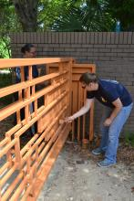 Navy Petty Officer First Class Brittney Waddell, left, and Navy Petty Officer First Class Annalynn Lawe paint the entrance gates at the Crosby Arboretum on May 8. About 20 Navy volunteers from the Stennis Space Center helped complete several large projects for the Picayune public garden before the arboretum's busy summer season.
