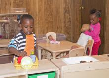 The children of Destiny's Day Care in Louisville, Mississippi, enjoy new classroom equipment in their temporary location on May 16, 2014, after the original site was destroyed by a tornado. With assistance from many, including MSU early care and education programs, the center reopened seven days after the storm. (Photo by MSU School of Human Sciences/Alicia Barnes)