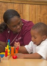 Mississippi State University Extension Service employee Tiffini Nash plays with a child on May 16, 2014, at Destiny's Day Care in Louisville, Mississippi, as part of disaster recovery assistance that included materials, supplies and personnel. (Photo by MSU School of Human Sciences/Alicia Barnes)