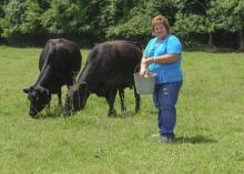 Sandy Coleman Mitchell feeds cattle at her family's farm in Corinth on July 14, 2014. Mitchell strives to educate her community about the importance of agriculture. (Photo by MSU Ag Communications/Kevin Hudson)