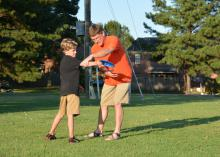 Eddie McReynolds of Starkville helps his 10-year-old son, Reece, develop his throwing skills for a game of disc golf. The McReynoldses practiced together near the Starkville Sportsplex on Sept. 3, 2014. (Photo by MSU Ag Communications/Linda Breazeale)