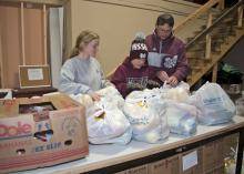 Holiday giving opportunities are an excellent time for parents to model generosity for their children. On Nov. 13, 2014, Mississippi State University student Heather Dodd, left, of Winona, prepares bags of groceries to be distributed to charity along with Latham Blake and his father, John Blake of Starkville. (Photo by MSU Ag Communications/Kat Lawrence)