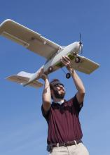 Lee Hathcock, a researcher and doctoral student at Mississippi State University, launches a Robota Triton unmanned aerial vehicle. (Photo by MSU Media Affairs/Beth Wynn)