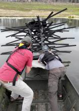 Mississippi State University students Jason Bies, left, and Clint Lloyd install an artificial, commercially-available fish habitat at Blackjack Pond on the MSU campus. (Photo by MSU Extension Service/Wes Neal)