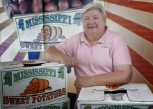 "Woman pictured with arms resting on boxes labeled ""Mississippi Sweet Potatoes."""
