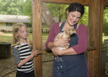 A woman holds a brown and white chicken while a young girl looks on.