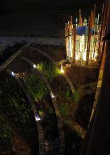 Light shines at night from a cylindrical, decorative garden feature, lighting a tiered landscape bed growing reed-like vegetation near a sidewalk.