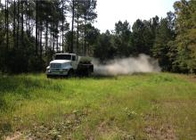 Dust billows out of a trailer on a large truck driving across a small, grassy area surrounded by tall trees.