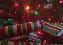 A stack of gifts wrapped in red, white and green stripes sits under a colorfully lit Christmas tree.