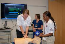 One teenager clasps both of her hands to press on a training manikin's chest, while another female student holds a ventilator mask over its face. A nurse in the background watches a large wall-mounted monitor.