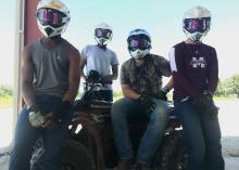 Four teenage boys wear helmets, goggles and gloves as they gather around an ATV.