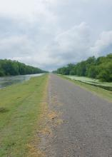 Gray pavement proceeds to the horizon bordered by a grass strip and then water to the tree line on both sides.