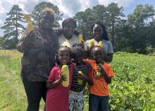 Two women and four children stand in a vegetable garden while holding yellow squash.