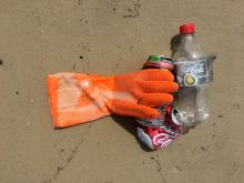 Small pile containing a rubber glove, an empty plastic bottle and two aluminum cans on wet sand.