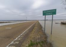 The view down a two-lane road with a wide expanse of water on each side and nearly touching the road. A road sign marks the Tallahatchie County line.