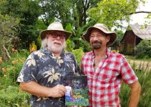 Two men in hats stand in a garden setting and hold a book on display.