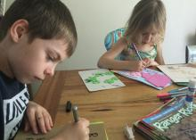 A boy and girl sit at a wooden table and use markers to draw on different colored sheets of paper.