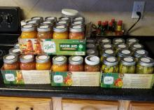 Glass canning jars filled with vegetables fill four boxes.