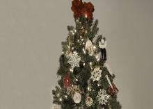 A Christmas tree is hung with red and white ornaments.