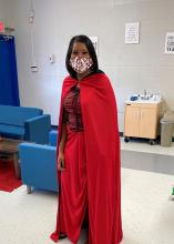 A woman in a red cape and mask stands in a classroom.