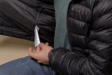 A hand holds onto the tag inside a garment.