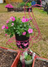 A pink flamingo made of wire holds a container with flowers.