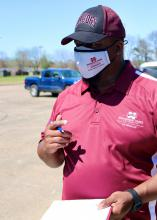 Man in maroon shirt and cap with a clipboard and pen.