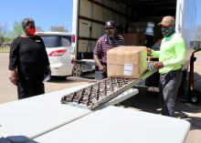 Three volunteers unload boxes from an 18-wheeler.