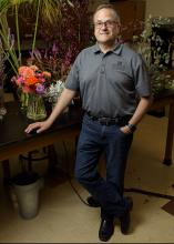 A man rests his hand on a table displaying floral arrangements.