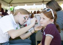 4-H, the youth development arm of the Mississippi State University Extension Service, took part in MSU's Homecoming celebration Oct. 20. 4-H'er Sara Burns of Lauderdale County paints the face of Rachel Singleton of Leflore County at a pregame tailgate party.  (Photo by MSU Ag Communications/Kat Lawrence)