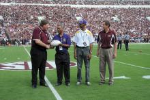 Mississippi State University Extension director Gary Jackson took to the field Sept. 7, 2013, at the MSU home opener to present a commemorative football to visiting Alcorn State University partners. From left are Jackson; Alcorn Extension administrators Dalton McAfee and Anthony Reed; and Gregory Bohach, MSU vice president for the Division of Agriculture, Forestry and Veterinary Medicine. (Photo by MSU Ag Communications/Kat Lawrence)