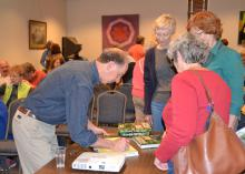 Horticulturist Rick Darke signs copies of his latest book for audience members after his presentation on balancing beauty and function in the home landscape March 28, 2015, in Picayune, Mississippi. Darke was the 2015 Mississippi State University Crosby Arboretum Lecture Series speaker. (Photo by MSU Ag Communications/Susan Collins-Smith)