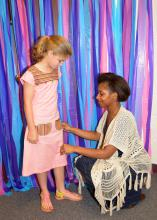 Mississippi State University student Iree Gordon of Jackson adjusts the dress she constructed for Oktibbeha County 4-H member Cory Freely before a special fashion show in Starkville, Mississippi, on May 2, 2015. (Photo by MSU Ag Communications/Linda Breazeale)