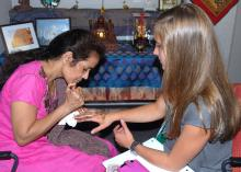 Aparna Krishnavajhala of India applies a henna tattoo on the hand of Ainsley Young, a Lee County 4-H member, during the first International Village, held during state 4-H Congress at Mississippi State University on May 27, 2015. (Photo by MSU Ag Communications/Linda Breazeale)
