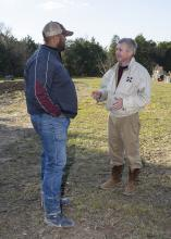 Scott Ross, right, talks with B.J. McClenton, an agent with the Mississippi State University Extension Service in Clay County, about his 50-acre pasture pig operation. (Photo by MSU Ag Communications/Kevin Hudson)