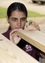 Tamara Amorim, a graduate student at Mississippi State University, measures a piece of lumber at the MSU Forest Products Laboratory as part of a large-scale research project designed to enhance the value of Southern forests. (MSU Extension Service/Kevin Hudson)