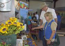 Lelia Kelly, a horticulture specialist with the Mississippi State University Extension Service, talks to a Sunbelt Ag Expo visitor about locally grown produce and Mississippi-made products on Oct. 22, 2015. (Photo by MSU Extension/Kevin Hudson)