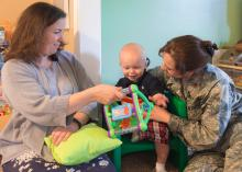 Heather Bond (left) plays with Thaddeus Pyko, while his mother, Maj. Kyla Pyko, watches. Bond is a family-home care provider who has opened her home to military families needing child care.  (Photo by MSU Extension Service/Alexandra Woolbright)