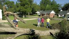 Mississippi State University Extension Service forestry associate John Auel demonstrates proper chainsaw equipment, techniques and apparel to use when removing an uprooted tree in Starkville, Miss., on Tuesday, Sept. 21, 2004. Homeowner Margaret Wade, her daughter, Debbie, and senior forestry major Dan Prevost of Raymond watch from a safe distance as the 50-year-old pecan tree is removed after Hurricane Ivan blew through the area with sustained winds in excess of 50 miles per hour. (AP Photo/Mississippi Sta