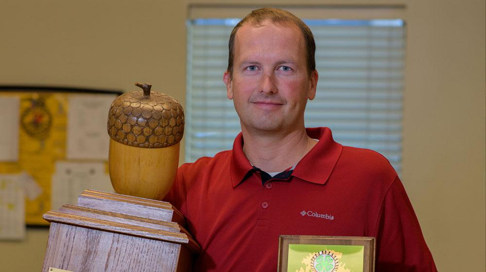 A man wearing a collared red shirt stands holding a large wooden trophy with a large wooden acorn on top in one hand and a plaque in the other.