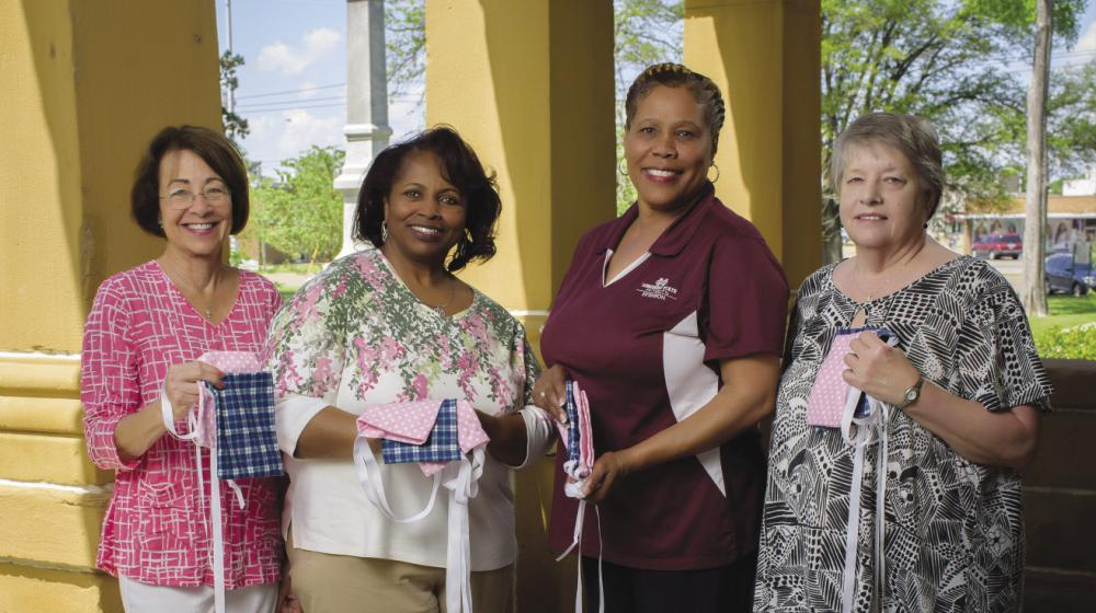 4 women holding mastectomy drain pouch bags—small, square sacks laced with ribbon