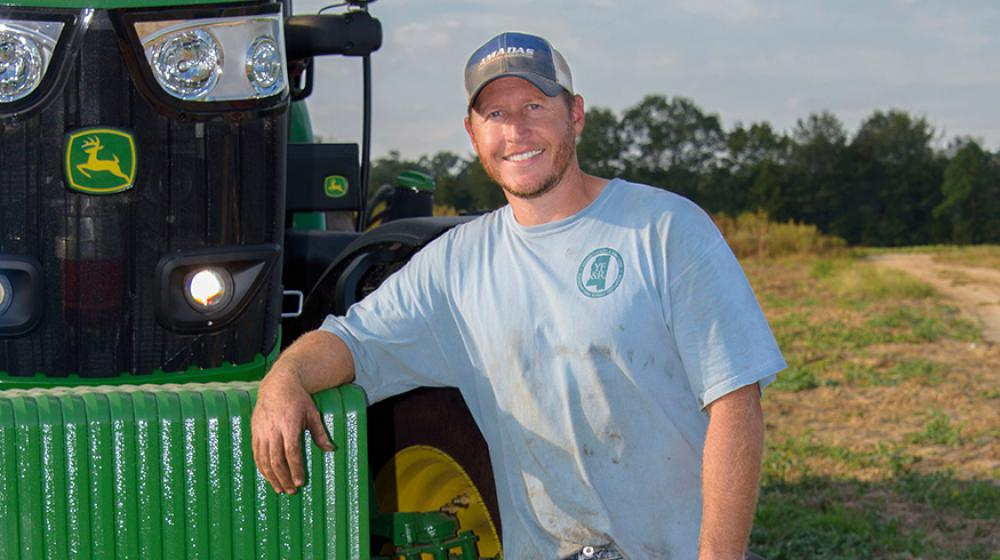 A man wearing a blue t-shirt and blue jeans leans against a green tractor.