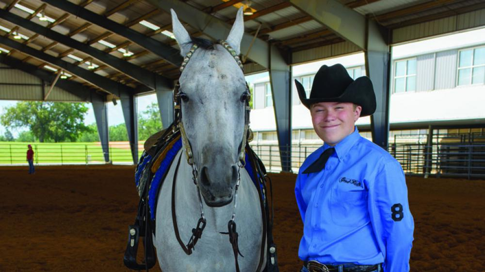 White horse stands beside teen boy with blue dress shirt and black cowboy hat