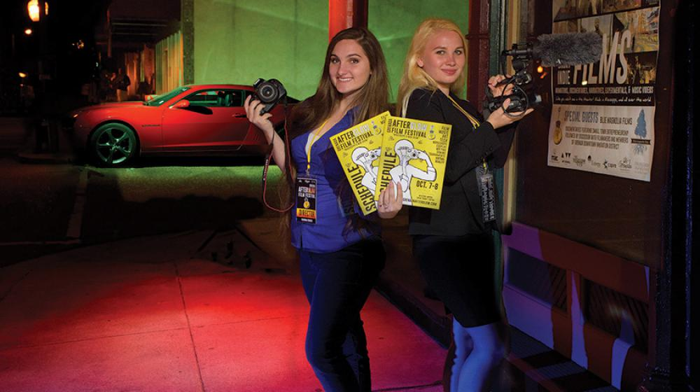 Two teenage girls holding cameras and yellow posters.