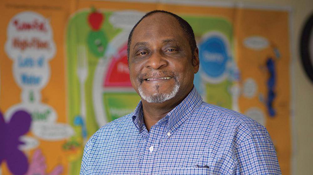 A smiling man wearing a blue checkered shirt.